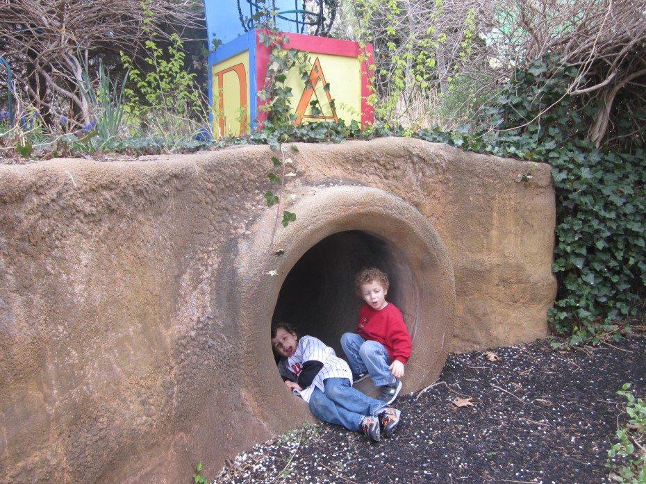 Children crawl through tunnels at the Camden Children's Garden