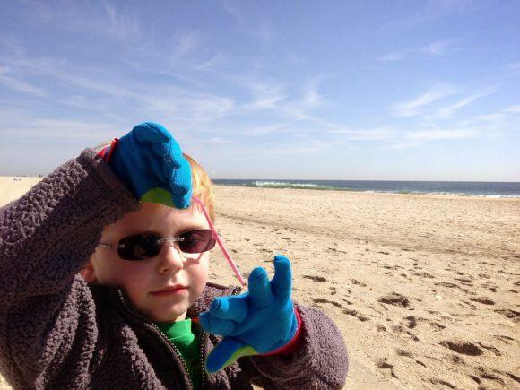 kid picking up trash at beach clean up