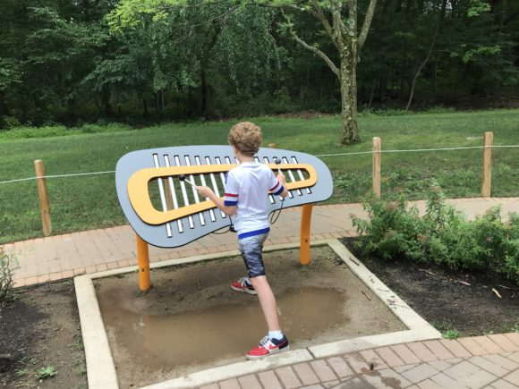 Child plays Xylophone in the central gazebo of the sensory trail at Trailside Nature Center