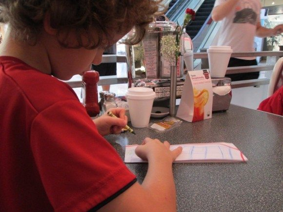 kid coloring while dining outside in New Jersey