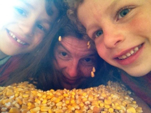 Mom and sons playing in the corn kernels at Sahls Father Son Farm in Galloway New Jersey