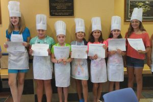 a group of girls from Kitchen Wizards summer camp dressed in chef aprons and hats