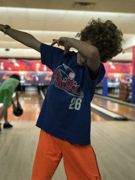 9 year old boy dabbing at bowling alley.