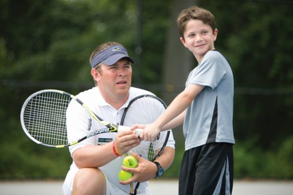 ESF camp boy learning to play tennis with coach