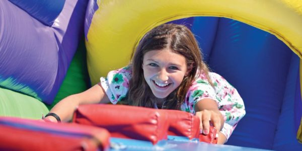 ESF camp girl climbing ladder in inflatable obstacle course
