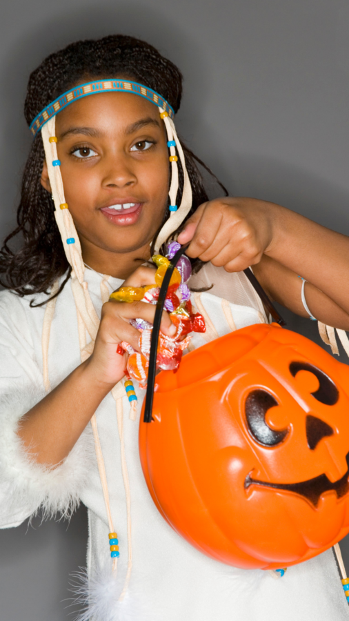 African american girl with a pumpkin bucket of candy to trade in