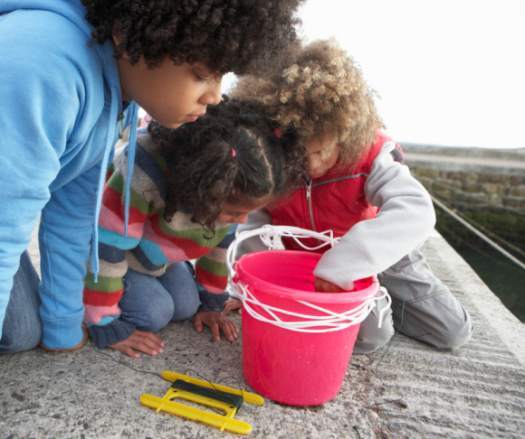 3 african american children look at fish caught in bucket