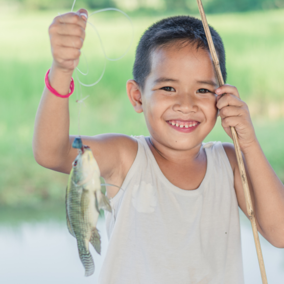 asian child holding a fish from fishing