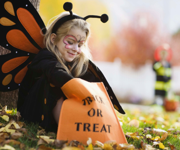 young girl in butterfly costume digs into an orange trick or treat bag