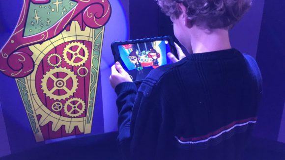 Boy uses ipad for virtual experience at Santa HQ