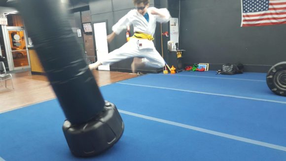 Mackenzie & Yates Martial Arts karate kid flies through the air with a kick.