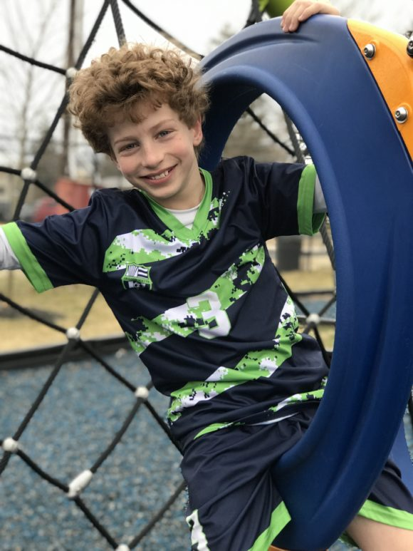 Sitting in one of the rings of the O-Zone Climber at Scott E Merulla Playground in Bellmawr
