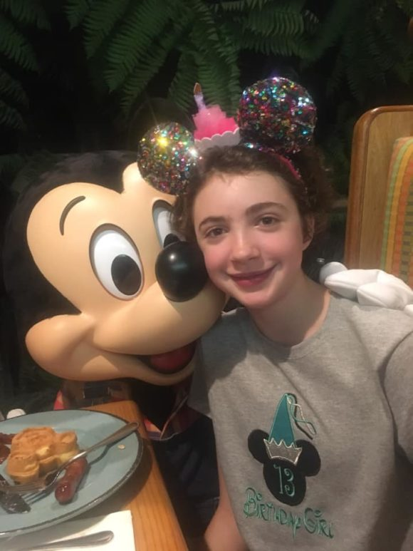 Teenager with Mickey Mouse at Disney World.