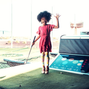 African american girl playing golf at a Topgolf summer golf camp