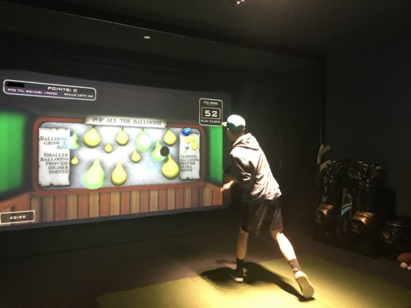 Teen plays pop the balloon carnival game at iPlay America's Topgolf suite