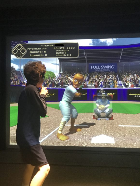 Teen pitches against a zombie in the Topgolf Baseball game at iPlay America.