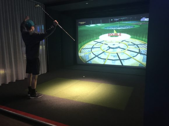 Teen plays golf in Topgolf Suite at iPlay America
