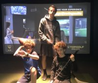 group picture of two teens and a tween in iplay america topgolf suite.
