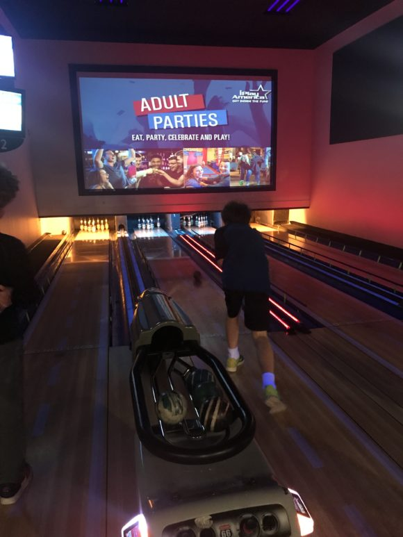 A teen bowls at the iPlay America bowling alley
