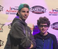 two teenagers in front of the iPlay America backdrop