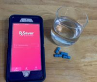 Picture of glass of water, medicine, and RS Saver app on phone