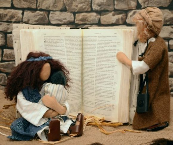 dolls holding a bible