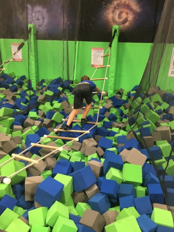Nj trampoline park boy climbing rope ladder over foam square pit
