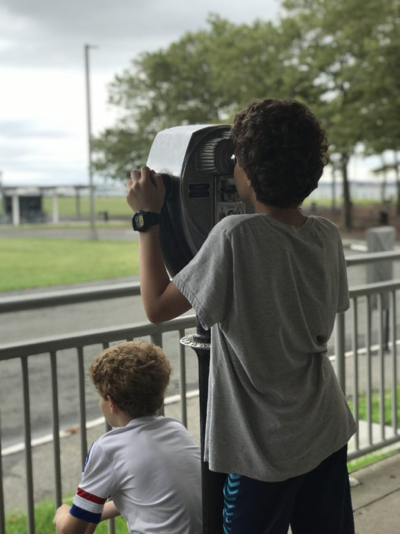 boy looks through viewfinder at Liberty State Park