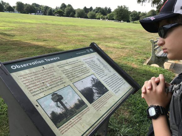 boy looks at signage about observation tower at Fort Mott State Park