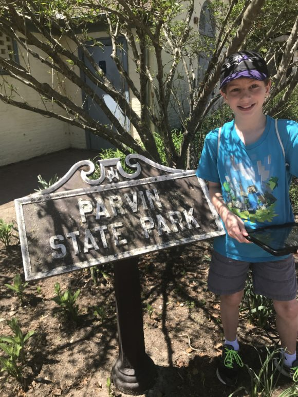 Boy at Parvin State Park sign