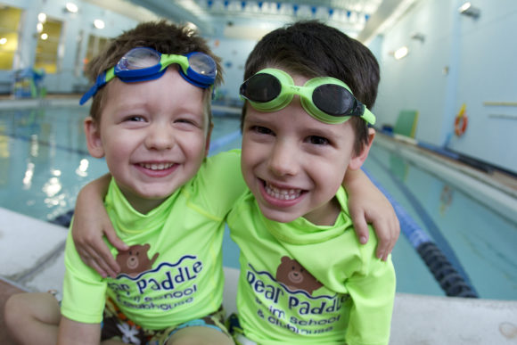 2 boys sit together on the poolside wearing bear paddle swim school shirts and goggles.