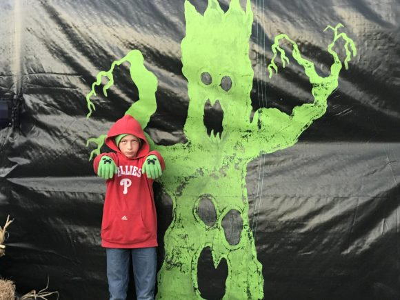 child poses with scary ghost in backdrop at Halloween Horror at Sahara Sam's