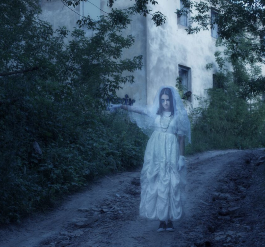 female ghosts walks down a pathway