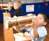 children look through a telescope in a museum