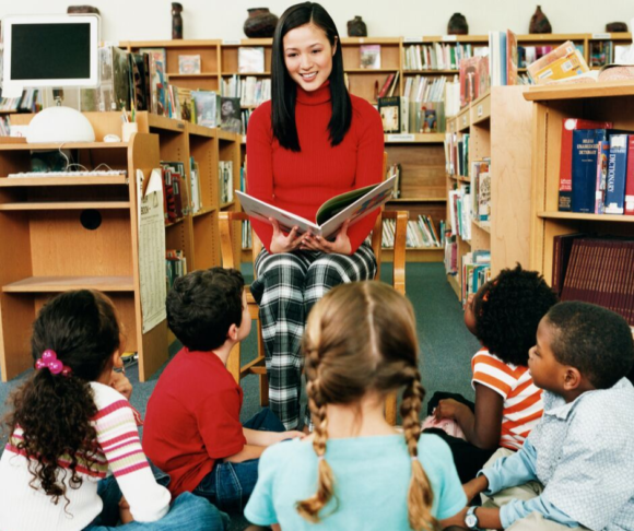 librarian reading a story book to children
