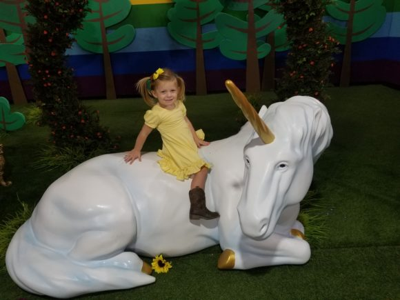 a little girl rides a unicorn at Happy Place Philadelphia