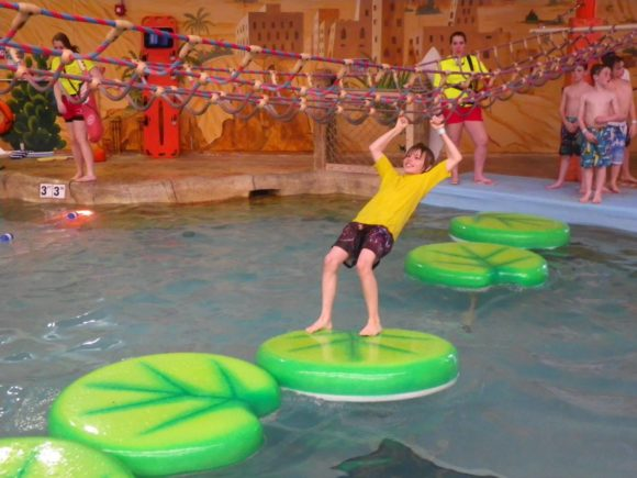 vboy going across lily pads at Sahara Sams indoor waterpark