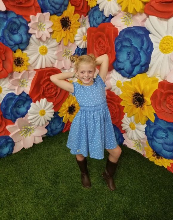 girl styling with flower wall at the Happy Place