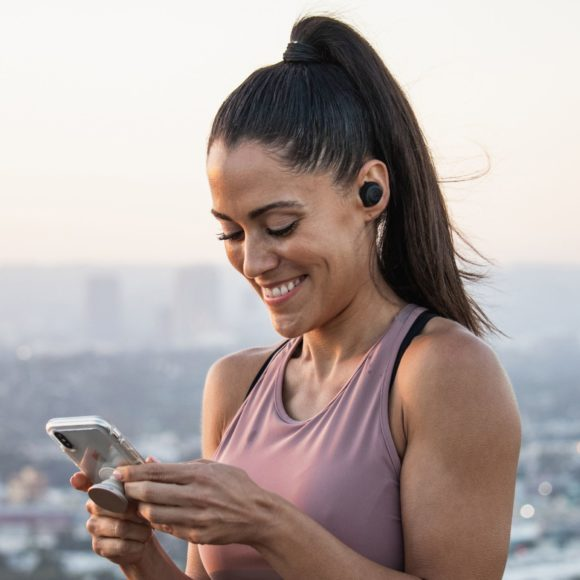 Female wearing JLab Audio - JBuds Air Icon while holding smart phone.