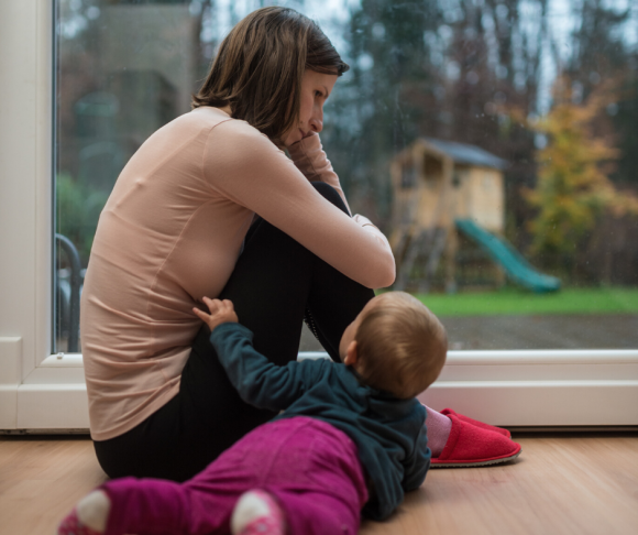 South Jersey mom at risk for postpartum depression stares out the window with baby at her side