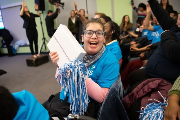 Comcast Digital Inclusion Rally Pennsylvania School for the Deaf happy female deaf student holds ipad and pom pom
