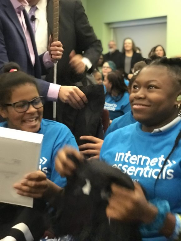 Two excited African American deaf female students from the Pennsylania school of the deaf are given ipads from Comcast.