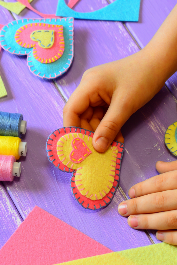child holds heart for valentine's day craft