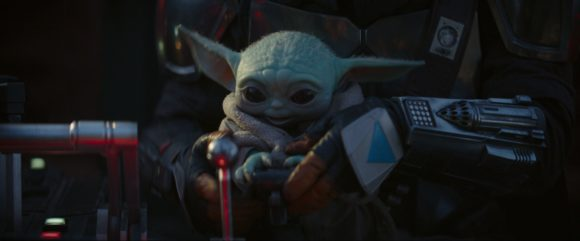 mando baby yoda looking happy and flying a plane