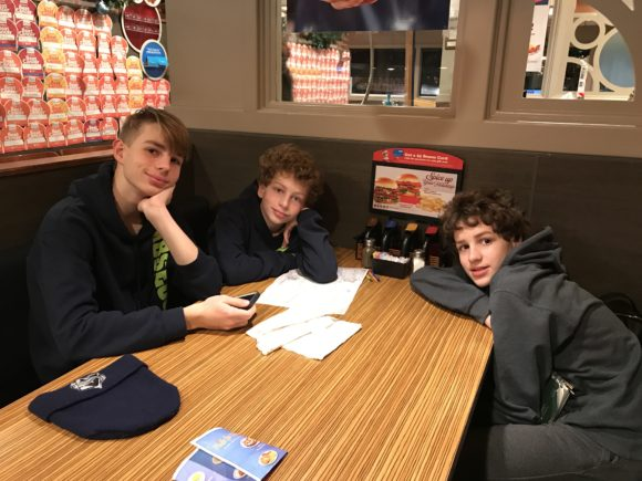 three boys sit in a booth at an IHOP restaurant in New Jersey
