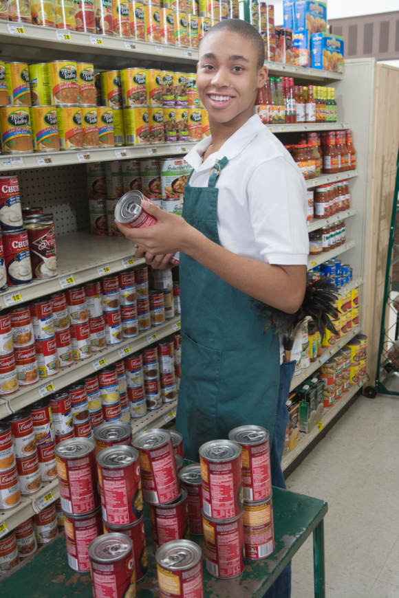black teenage male works to stock shelves in a grocery store