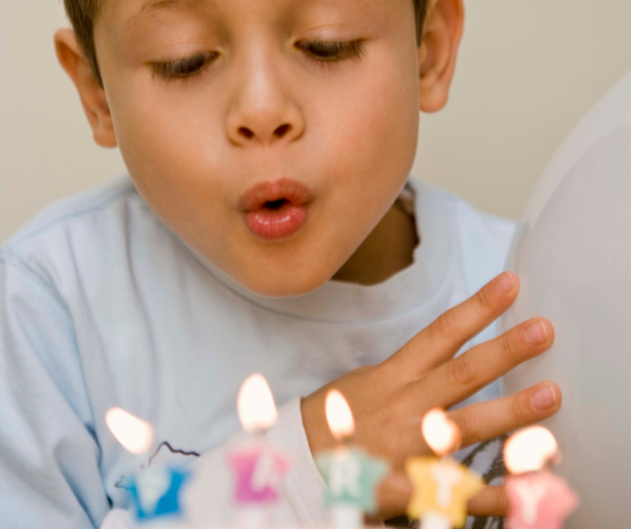 child blows out candles on a delivered birthday cake