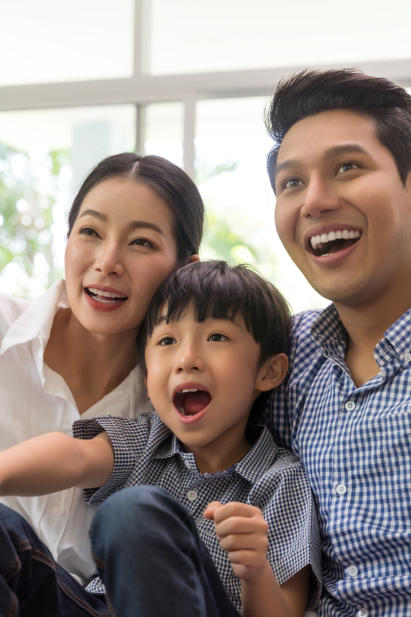 Asian parents with child watching a movie