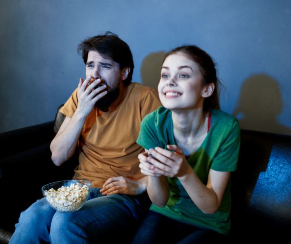 Father and daughter watch a movie while eating popcorn