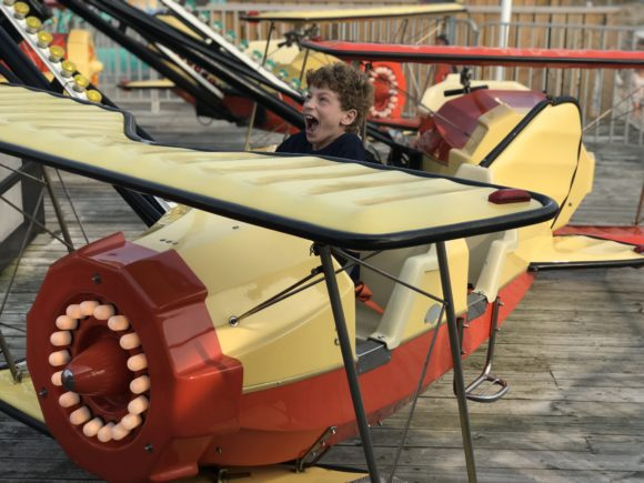 Boy flies in airplane ride at Mariner's Amusement Pier, one of Morey's Piers piers.